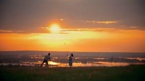 Fille et type jouant le badminton sur le champ, se tenant à côté de leur petit fils, soirée d'été de coucher du soleil clips vidéos