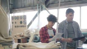 Fille et type marchant dans l'atelier en bois parlant tenant les documents sur papier de comprimé et banque de vidéos