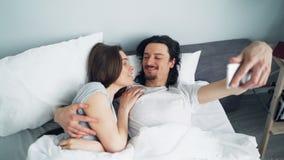 Fille et type prenant le selfie dans le lit avec étreindre de baiser de caméra de smartphone banque de vidéos