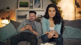 Fille et type regardant la TV discuter les nouvelles parlant, homme utilisant le smartphone à la maison banque de vidéos