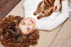 Fille et un chat se trouvant sur le divan Images stock