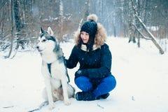 Fille et un chien dans la forêt d'hiver images stock