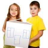 Fille et un garçon rêvant d'une maison neuve Photos stock