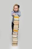 Fille et une pile grande de livres Photographie stock