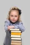 Fille et une pile grande de livres Image libre de droits