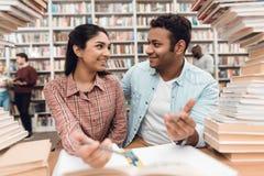 Fille ethnique et type indiens de métis entourés par des livres dans la bibliothèque Les étudiants prennent des notes Photos stock