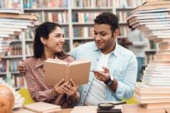 Fille ethnique et type indiens de métis entourés par des livres dans la bibliothèque Les étudiants reding le livre Images stock