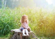 Fille européenne aux cheveux bouclés de trois ans étreignant un lapin en parc d'été Photographie stock libre de droits