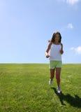 Fille exécutant sur l'herbe Photographie stock libre de droits