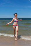 Fille exécutant sur la plage Image stock