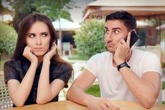 Fille fâchée écoutant son ami parlant au téléphone Photographie stock