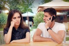 Fille fâchée écoutant son ami parlant au téléphone Photographie stock libre de droits