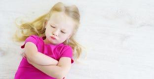 Fille fâchée se trouvant sur le plancher en bois blanc images libres de droits