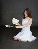 Fille - fée avec la baguette magique et le livre magiques dans des mains Photos stock