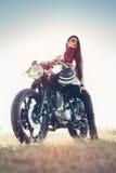 Fille féminine de cycliste de mode Jeune femme s'asseyant sur la motocyclette de coutume de vintage photos stock