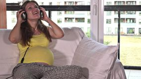 Fille féminine enceinte heureuse appréciant la musique avec son bébé à venir s'asseyant sur le sofa banque de vidéos