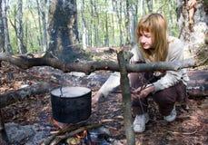 Fille faisant cuire la nourriture sur l'incendie dans le camp Photos stock