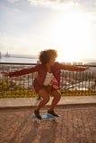 Fille faisant de la planche à roulettes sur un pont pavé Photos libres de droits