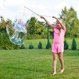 Fille faisant des bulles de savon dans le jardin Image stock
