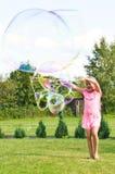 Fille faisant des bulles de savon dans le jardin Images libres de droits