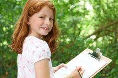 Fille faisant des notes sur l'excursion sur le terrain de nature d'école Images libres de droits
