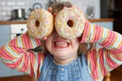 Fille faisant des verres utilisant les beignets sucrés images stock