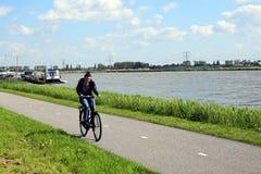 Fille faisant du vélo contre le vent contraire de te dans le paysage néerlandais photos stock