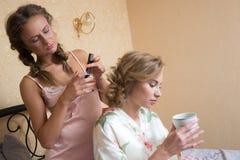 Fille faisant l'amie de coiffure dans le lit bedroom Image stock