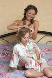 Fille faisant l'amie de coiffure dans le lit bedroom Photo stock