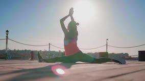 Fille faisant la ficelle fendue Hanumanasana, pose de singe Le yoga practic de femme, sport, concept sain de mode de vie clips vidéos