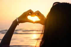 Fille faisant la forme de coeur avec des mains dans le coucher du soleil Photo stock