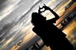 Fille faisant la forme de coeur dans le coucher du soleil Photos stock