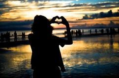 Fille faisant la forme de coeur dans le coucher du soleil Images stock