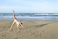 Fille faisant la roue sur la plage Photographie stock