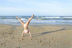 Fille faisant la roue sur la plage Photos libres de droits