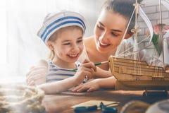 Fille faisant le bateau modèle photo stock