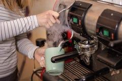 Fille faisant le caf? d'expresso sur une machine professionnelle dans la barre photos libres de droits