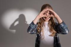 Fille faisant le geste et la position d'amour dans le studio avec l'ombre en forme de coeur Image stock