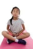 Fille faisant le meditaion sur le tapis rose de yoga avec le fond blanc Image stock