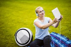 Fille faisant le selfie sur le comprimé se reposant sur l'herbe en parc Est tout près elle monoclean Elle ` s écoutant la musique Image libre de droits