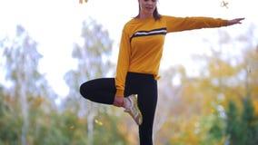 Fille faisant le support acrobatique, essayant de garder l'équilibre Gymnaste sur la formation Automne banque de vidéos