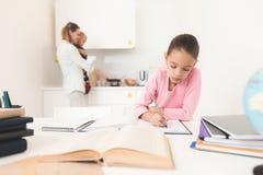 Fille faisant le travail dans la cuisine Elle regarde pensivement dans le manuel Photos libres de droits