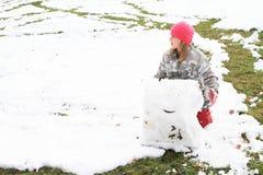 Fille faisant une grande boule de neige Photographie stock libre de droits