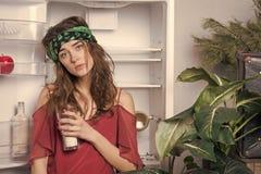 Fille fatiguée avec le verre de lait au réfrigérateur dans la cuisine Femme sensuelle au r?frig?rateur ouvert Femme de beauté ave images libres de droits