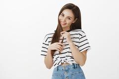 Fille Flirty essayant de convaincre la pizza d'ordre d'ami Portrait de studio de femme féminine mignonne dans le T-shirt rayé Photo libre de droits