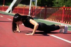 Fille forte d'athlète faisant l'exercice de planche extérieur au pont i photo stock