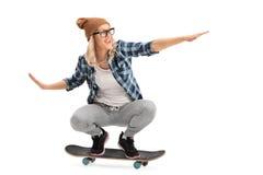 Fille fraîche de patineur montant une planche à roulettes photographie stock libre de droits