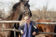 Fille frottant un cheval de pur sang dans le stylo pour le pré Images libres de droits