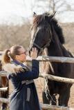 Fille frottant un cheval de pur sang dans le stylo pour le pré Photos stock