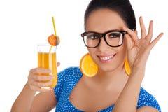 Fille futée avec le jus d'orange et le fond orange de blanc de boucles d'oreille de tranche Photographie stock libre de droits